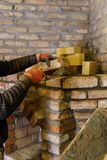 The builder lays down the bricks for the fireplace and fastens them with cement mortar stock photo