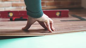 A builder lays laminate flooring in a new apartment. The concept of home repair.
