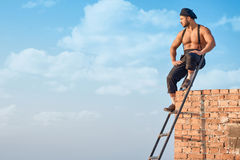 Builder leaning on brick wall on high. Royalty Free Stock Image