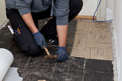 Builder lifting old floor tiles in a passage Royalty Free Stock Photography