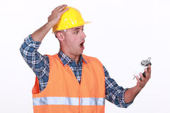 Builder looking at alarm clock Royalty Free Stock Photo