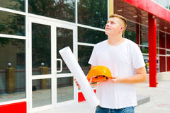 Builder looking at a building with a smile Royalty Free Stock Image
