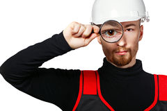 Builder looking through a magnifying glass Royalty Free Stock Photos