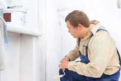 Builder looking at the paint wall Royalty Free Stock Photos