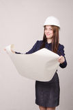Builder looking project, deploying hands drawing. Young woman architect in hardhat standing with blueprints in hand stock photo