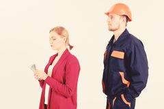 Builder looks at woman with busy face counting money,. Builder in helmet looks at woman with busy face counting money, isolated on white background. Repairer royalty free stock image