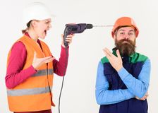 Builder makes hole in male head. Husband annoyed by wife. Carefree and relaxed concept. Woman drills head of man, white background. Man in helmet with carefree stock images