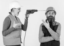Builder makes hole in male head. Husband annoyed by wife. Carefree and relaxed concept. Woman drills head of man, white background. Man in helmet with carefree royalty free stock photography