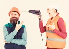 Builder makes hole in male head. Husband annoyed by wife. Carefree and relaxed concept. Woman drills head of man, white background. Man in helmet with carefree royalty free stock images