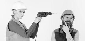Builder makes hole in male head. Suffer and tolerate concept. Woman drills head of man, white background. Man in helmet with carefree face ignoring his wife royalty free stock image