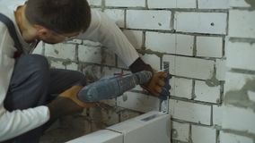 Builder making holes in brick wall with electric drill to fix joining clamp. Worker building interior wall at construction site. House renovation, building and stock video