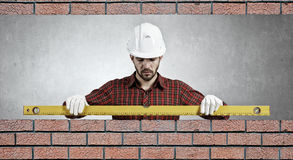 Builder man with level . Mixed media Royalty Free Stock Image