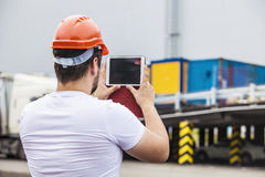 Builder man working with a tablet in a protective helmet Stock Photos