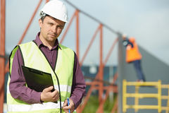 Builder manager worker at construction site. Site manager worker in uniform and safety protective equipment in front of metal construction frames Stock Photo