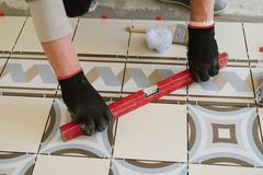 The builder-mason controls the level of the horizontal tile with Royalty Free Stock Photo