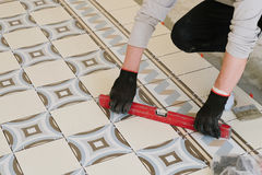 The builder-mason controls the level of the horizontal tile with Royalty Free Stock Photos