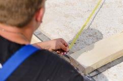 Builder measuring a diagonal Stock Image