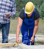 Builder measuring a wooden beam Stock Image