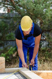 Builder measuring a wooden beam Royalty Free Stock Photography