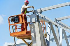 Builder millwright worker at construction site. Worker joiner in uniform and safety protective equipment at metal construction frames installation and assemblage Stock Photo