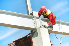 Builder millwright worker at construction site. Worker in uniform and safety protective equipment at metal construction frames installation and assemblage Stock Images