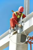 Builder millwright worker at construction site. Worker in uniform and safety protective equipment at metal construction frames installation and assemblage Royalty Free Stock Image