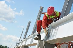 Builder millwright worker at construction site. Worker in uniform and safety protective equipment at metal construction frames installation and assemblage Stock Image