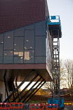 Builder On A Scissor Lift Platform At A Construction Site Stock Photo