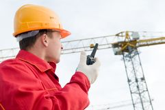 Builder operating the tower crane Royalty Free Stock Photo