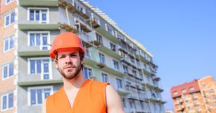 Builder in orange vest and helmet works construction site. Safety of builder at work concept. Guy in protective helmet royalty free stock photography