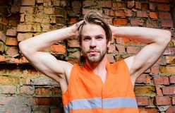 Builder orange vest work construction site. macho foreman. Builder muscular arms macho dream of every woman. Guy tousled hair stand in front of wall made out stock image