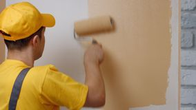 Builder paints white wall. Builder paints white wall in beige color with a roller