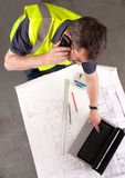 Builder phones about construction blueprint. Builder on phone checks blueprint and uses laptop. Focus on face. Elevated view Royalty Free Stock Image