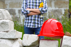 Builder in a plaid shirt. Helmet and stonework. stock images