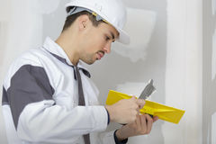 Builder plastering cement on wall Stock Photos