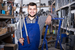 Builder  with pleasure showing his workplace. Smiling builder with pleasure showing his workplace in workshop Royalty Free Stock Photo