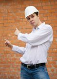 Builder  pointing to brick wall Royalty Free Stock Image