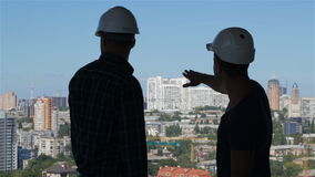 Builder points his hand at the complex of high buildings. Young builder pointing his hand at the complex of high buildings from the building under construction stock video