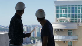 Builder points at the penthouse near the building under construction. Caucasian builder pointing his hand at the penthouse near the building under construction stock video footage
