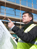 Builder points up at construction site. Architect or engineer at work on a building site. Holding plans for construction work. Confident gaze. Points up to part Stock Image