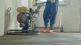 Mechanized grout screed concrete floor close-up. Builder polishing mortar floor at construction site of new appartments. Mechanized grout screed concrete floor Stock Photos