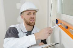 Builder posing and pointing to spirit level Royalty Free Stock Photography