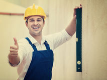 Builder posing with spirit level Royalty Free Stock Images