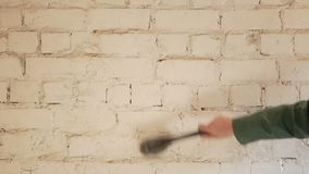 The builder prepares the wall before painting. By rubbing it with a brush stock video footage