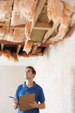 Builder Preparing Quote For Damage To Ceiling Royalty Free Stock Photos