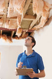 Builder Preparing Quote For Damage To Ceiling Royalty Free Stock Image