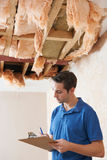 Builder Preparing Quote For Damage To Ceiling Royalty Free Stock Images