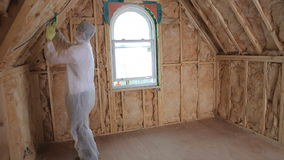 Builder in protecive suit insulating house stock video footage