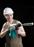The builder in a protective helmet holds the profe Royalty Free Stock Images
