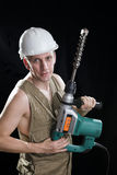 The builder in a protective helmet holds the profe Stock Image